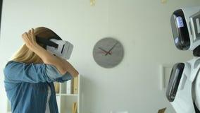 Robotic maskin som ger flickavirtuell verklighethörlurar med mikrofon stock video