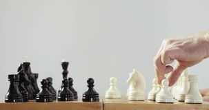 Robotic prosthetics hand is playing chess with human hand. Artificial intelligence concept. Side view, hands close-up stock footage