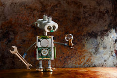 Robotic toy character lamp in hand, rusty iron surface. Vintage textured wall backdrop. Shallow depth field. Royalty Free Stock Photo