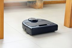 Robotic vacuum cleaner on bright tiled floor royalty free stock photo