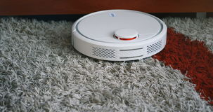 Robotic vacuum cleaner on carpet rug floor smart cleaning technology stock footage