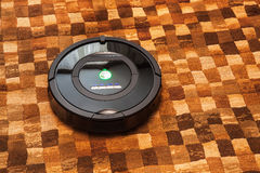 Robotic vacuum cleaner on carpet Royalty Free Stock Image