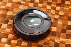 Robotic vacuum cleaner on carpet Stock Photography