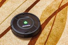 Robotic vacuum cleaner on carpet Stock Images