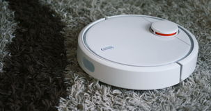 Robotic vacuum cleaner on carpet - technology housework stock video footage