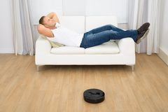 Robotic vacuum cleaner in front of man relaxing Royalty Free Stock Photography