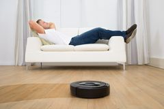 Robotic vacuum cleaner in front of man relaxing Stock Images