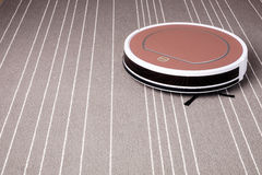 Robotic vacuum cleaner on grey carpet smart cleaning technology Royalty Free Stock Images