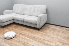 Robotic vacuum cleaner on laminate floor near sofa closeup, smart home robotics wireless cleaning for simplify routine housework,. Efficient dust absorption in stock images