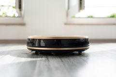 Robotic vacuum cleaner on laminate wood floor Stock Photography