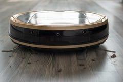 Robotic vacuum cleaner on laminate wood floor Stock Photos