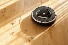 Robotic vacuum cleaner on laminate wood floor smart cleaning tec Stock Photo