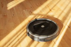 Robotic vacuum cleaner on laminate wood floor smart cleaning tec. Hnology Stock Photo