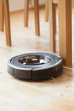 Robotic vacuum cleaner on laminate wood floor smart cleaning tec. Hnology Royalty Free Stock Photos
