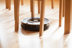 Robotic vacuum cleaner on laminate wood floor smart cleaning tec. Hnology Royalty Free Stock Photo