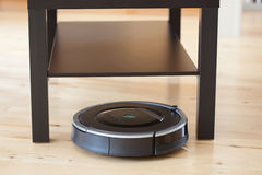 Robotic vacuum cleaner on laminate wood floor smart cleaning tec. Hnology Stock Photography