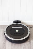 Robotic vacuum cleaner on laminate wood floor smart cleaning tec Stock Images