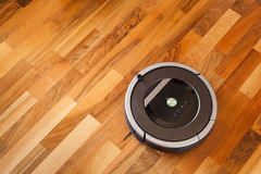 Robotic vacuum cleaner on laminate wood floor smart cleaning tec. Hnology Royalty Free Stock Photography
