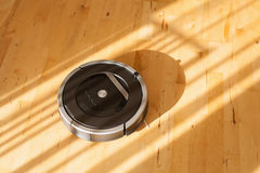 Robotic vacuum cleaner on laminate wood floor smart cleaning tec. Hnology Stock Photos