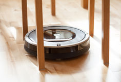 Robotic vacuum cleaner on laminate wood floor smart cleaning tec. Robotic vacuum cleaner on laminate wood floor smart cleaning  technology Royalty Free Stock Images