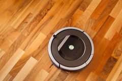 Robotic vacuum cleaner on laminate wood floor smart cleaning tec. Hnology Stock Images