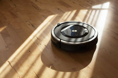 Robotic vacuum cleaner on laminate wood floor smart cleaning tec. Hnology Royalty Free Stock Image