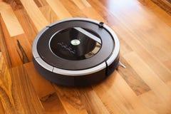 Robotic vacuum cleaner on laminate wood floor smart cleaning tec Stock Photos