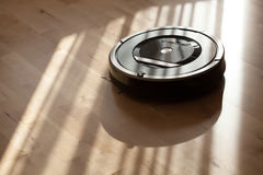 Robotic vacuum cleaner on laminate wood floor smart cleaning tec Royalty Free Stock Photos