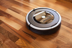 Robotic vacuum cleaner on laminate wood floor smart cleaning tec. Hnology Royalty Free Stock Images