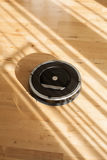 Robotic vacuum cleaner on laminate wood floor smart cleaning tec Stock Images