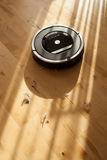 Robotic vacuum cleaner on laminate wood floor smart cleaning tec. Hnology dust Stock Image
