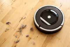 Robotic vacuum cleaner on laminate wood floor smart cleaning tec Stock Photos