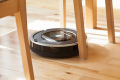 Robotic vacuum cleaner on laminate wood floor smart cleaning tec. Hnology problem Stock Photo