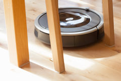Robotic vacuum cleaner on laminate wood floor smart cleaning tec. Hnology problem Stock Photos