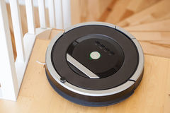 Robotic vacuum cleaner on laminate wood floor smart cleaning tec. Hnology stairs Royalty Free Stock Images