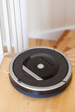 Robotic vacuum cleaner on laminate wood floor smart cleaning tec. Hnology stairs Stock Photos