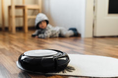 Robotic vacuum cleaner on little white carpet Royalty Free Stock Image