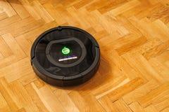 Robotic vacuum cleaner on parquet Stock Photos