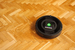 Robotic vacuum cleaner on parquet Stock Photography