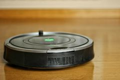 Robotic vacuum cleaner cleaning under the sofa, technological progress, matte effect royalty free stock photography