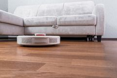 Robotic vacuum cleaner runs near sofa on laminate floor. Robot controlled by voice commands to direct cleaning. Modern smart. Cleaning technology, efficient royalty free stock photos