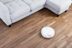 Robotic vacuum cleaner runs near sofa on laminate floor. Robot controlled by voice commands to direct cleaning. Modern smart stock photo