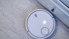 A robotic vacuum moving along white drawers in a smart house. 4K. stock video