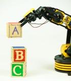 Robotics ABCs. An educational robot arm builds with alphabet building blocks Royalty Free Stock Image
