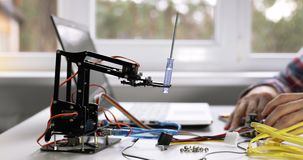 Robotics engineering - technician programming robot arm on computer. In office stock video footage
