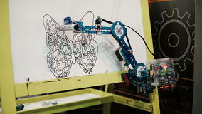 Robotics Expo. Robot draws the stencil, mechanical arm with calligraphy handwriting. 4K stock video footage