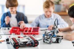Robots confeccionados en la tabla delante de muchachos Imagenes de archivo