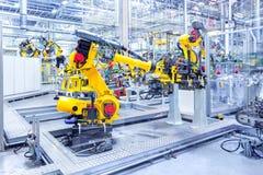 Robots in een autoinstallatie stock foto