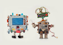 Robots friends Funny man mechanism with monitor head, love heart abstract message on screen Woman robot green circuit Royalty Free Stock Photos