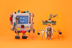 Robots friends ready for service repair. Funny robotic characters with instrument, pliers hand wrenches. Smile message. Blue screen monitor, cyborg electric Stock Photography